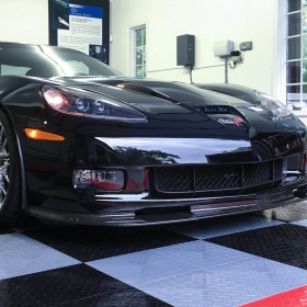 RaceDeck Diamond Tuffshield black, gray, and red garage floor tiles showcases a black Corvette.