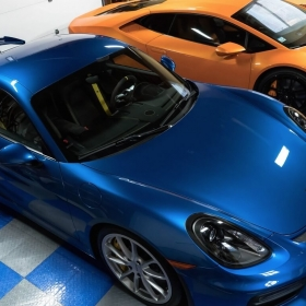 RaceDeck Diamond Tuffshield garage flooring in royal blue and alloy complements these blue and orange cars.