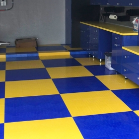 Featured on the Vanilla Ice Project: Garage with RaceDeck Diamond Tuffshield flooring in royal blue and yellow.