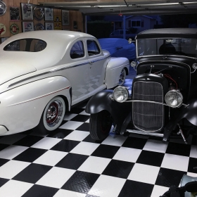 Black and white vintage cars on checkerboard garage floor.
