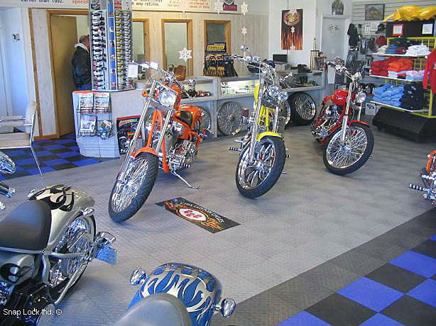 Motorcycles in a display with RaceDeck Diamond alloy, graphite, royal blue and black flooring.