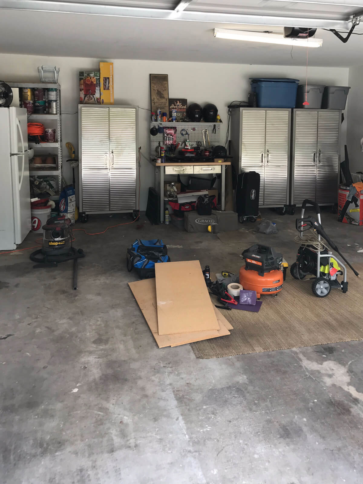 Before: a home garage with a stained concrete floor.