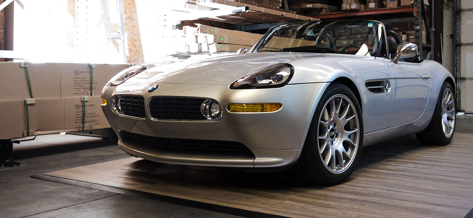 A BMW Z3 parked on Smoked Oak display flooring and on display in a warehouse.