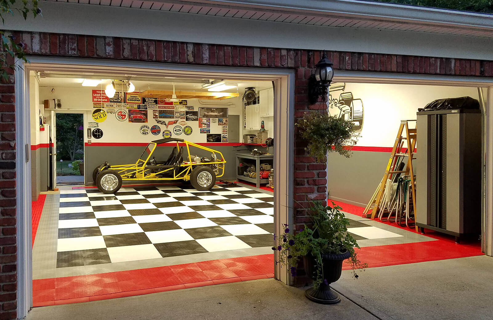 """Looking in at a garage with RaceDeck Diamond<sup>™</sup> flooring and red edging. <a href=""""http://racedeck.com/racedeck-products/racedeck-diamond/"""">Click here for more about RaceDeck Diamond. </a>"""