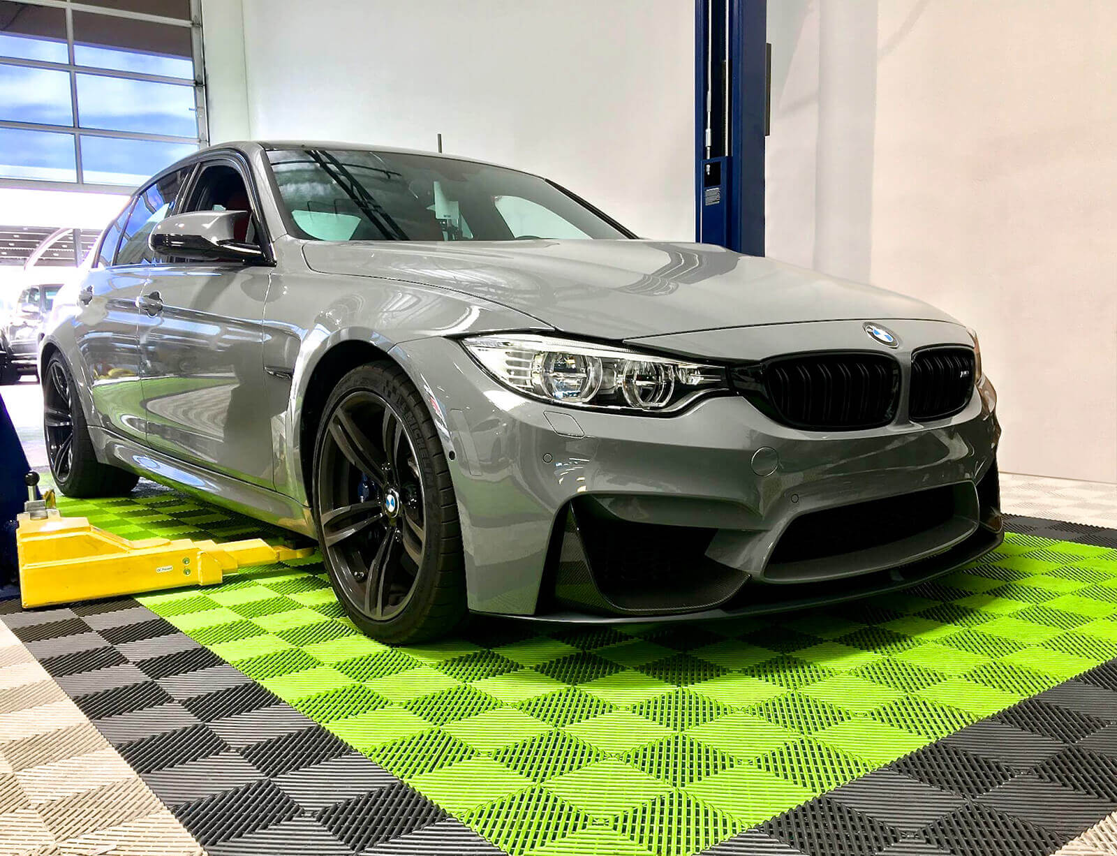 BMW on Free-Flow sublime, graphite and white tile flooring at Lusso Auto Spa.