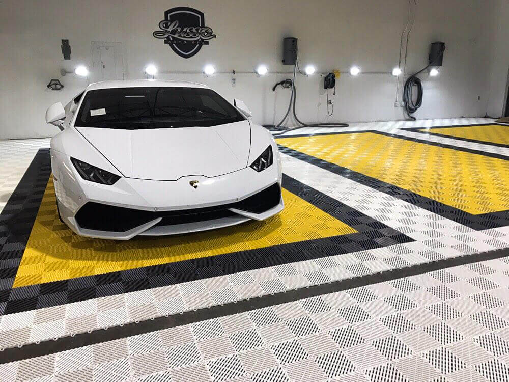 """Lambo on self-draining Free-Flow in white, black and yellow at Lusso Auto Spa. <a href=""""http://racedeck.com/racedeck-products/free-flow/"""">Click here for more about Free-Flow.</a>"""