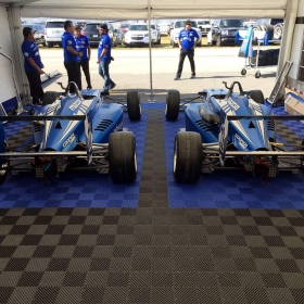 Black and royal blue Free-Flow garage floor tiles in this racing tent.