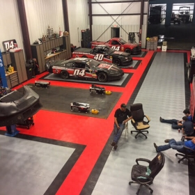 Red, alloy and black RaceDeck Diamond flooring in a race car shop.