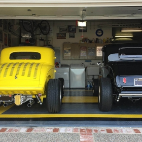 Vintage cars in a matching yellow, black and alloy RaceDeck Diamond-floored garage.
