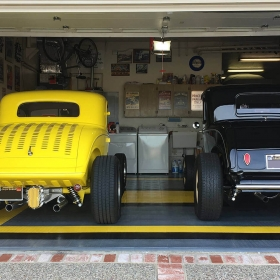 Classic black and yellow cars in a matching garage with RaceDeck Diamond garage flooring.