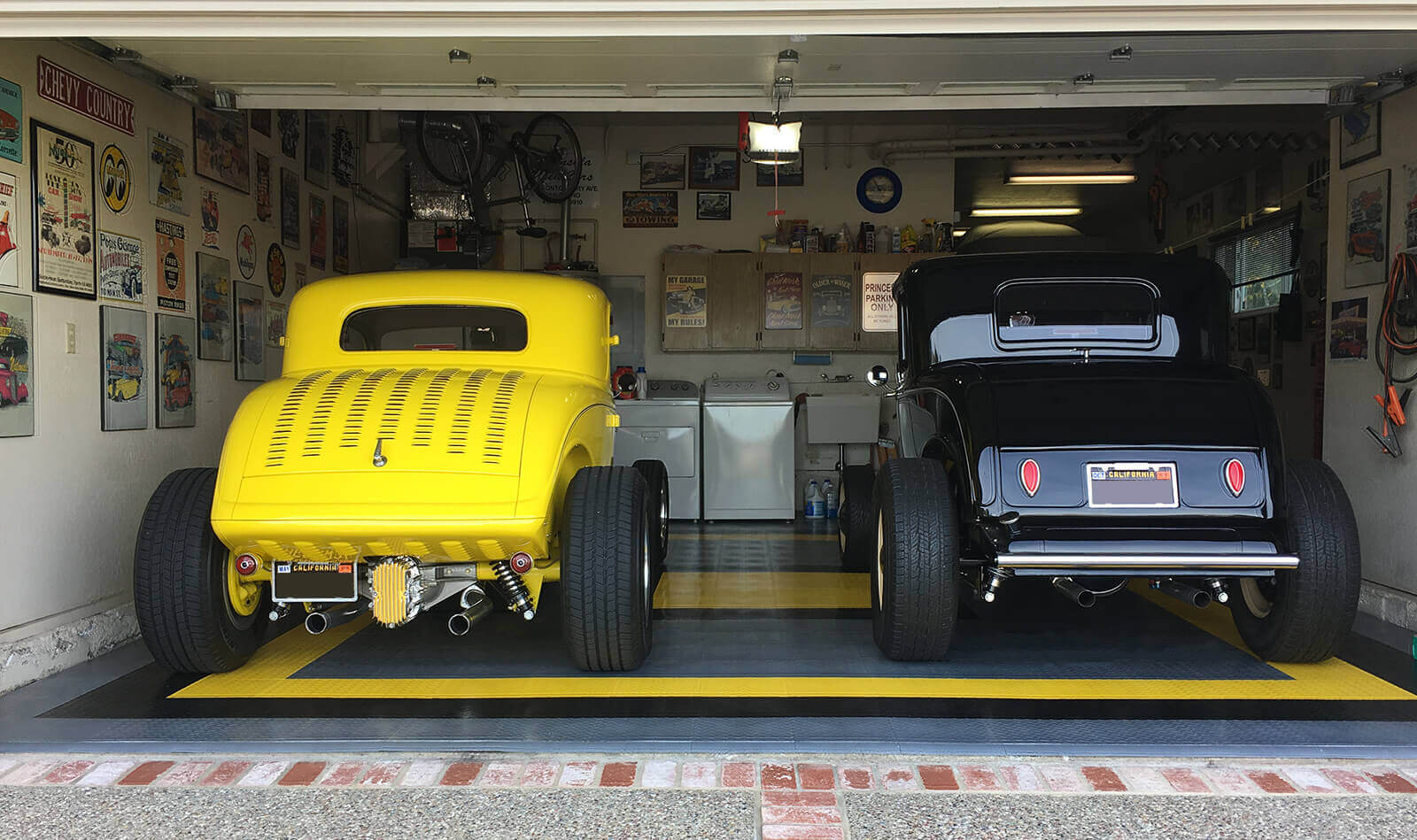 """Classic black and yellow cars in a matching garage with RaceDeck Diamond flooring. <a href=""""http://racedeck.com/racedeck-products/racedeck-diamond/""""> Click here for more about RaceDeck Diamond.</a>"""