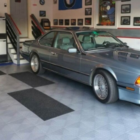 BMW in a garage with RaceDeck Diamond flooring with edging and carpet mats atop.