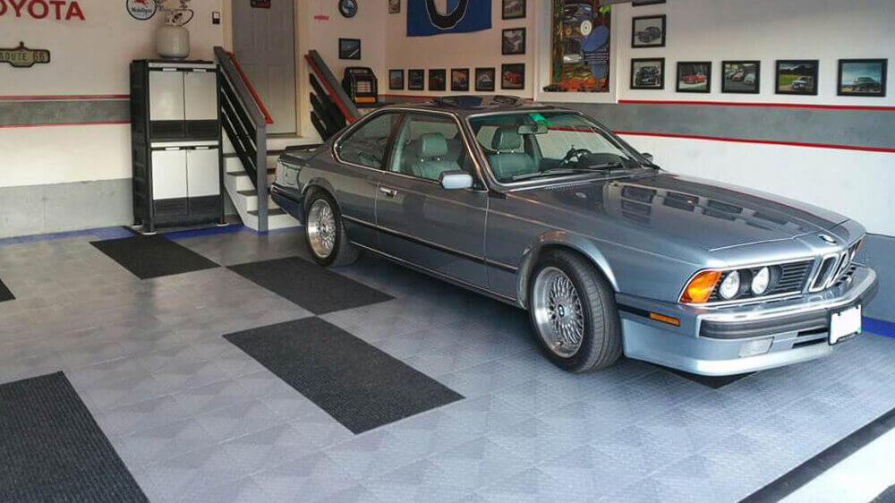 """BMW in a garage with RaceDeck Diamond flooring with edging and carpet mats atop. <a href=""""http://racedeck.com/racedeck-products/racedeck-diamond/"""">Click here for more about RaceDeck Diamond.</a>"""