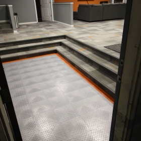 RaceDeck Diamond modular floor accent with alloy and orange.
