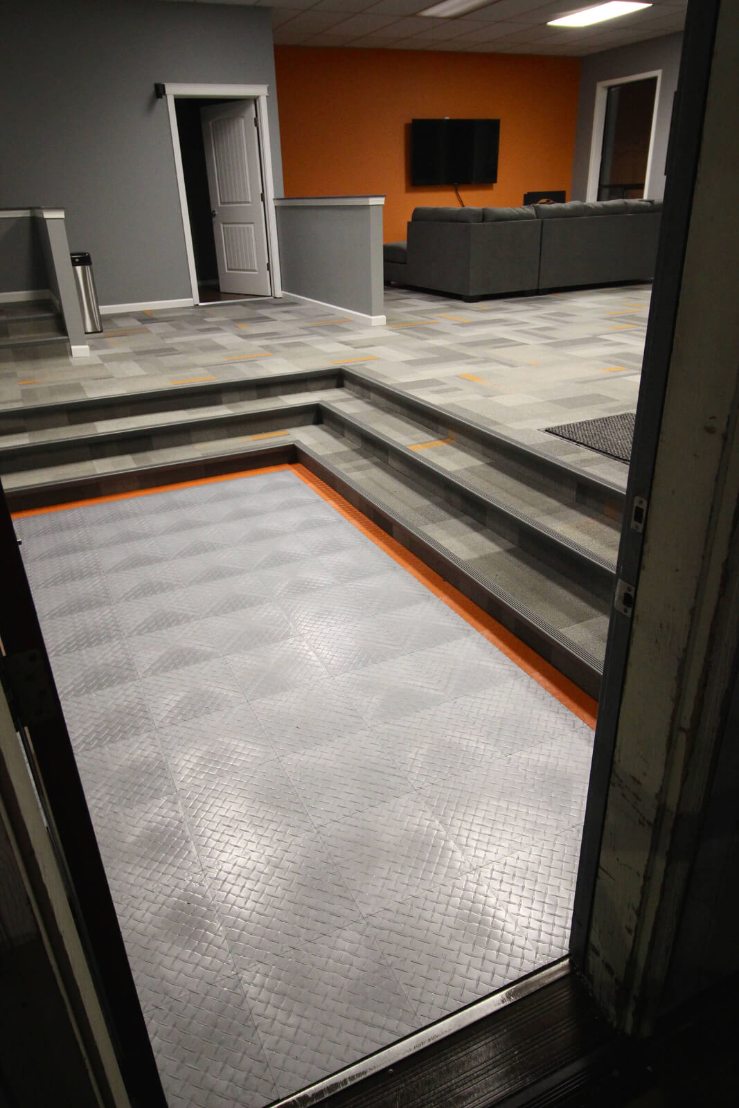 """RaceDeck Diamond floor accent with alloy and orange. <a href=""""http://racedeck.com/racedeck-products/racedeck-diamond/"""">Click here for more about RaceDeck Diamond.</a>"""