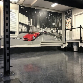 TuffShield high-gloss finish on the graphite and black RaceDeck Diamond flooring in this monochrome garage.