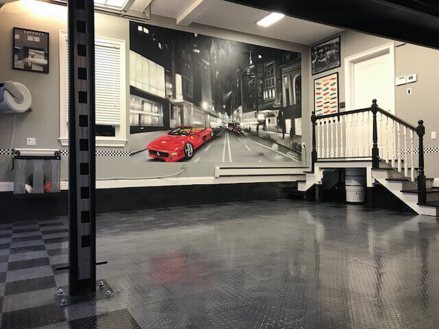 """Graphite and black RaceDeck Diamond<sup>™</sup> with TuffShield<sup>®</sup> high-gloss finish in a garage with a lift. <a href=""""http://racedeck.com/racedeck-products/tuffshield/"""">Click here for more about TuffShield.</a>"""