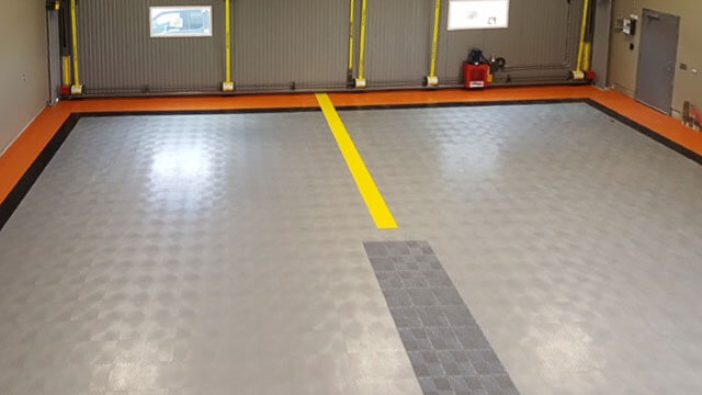 View inside a hangar with RaceDeck Diamond flooring in multiple colors.