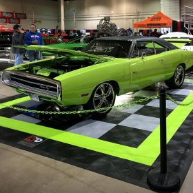 A car show display with RaceDeck Diamond and a Dodge Charger RT.