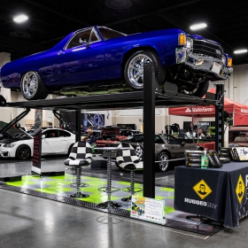 A RaceDeck display floor with a four post lift and an El Camino. The display features RaceDeck Diamond with TuffShield garage floor tiles.