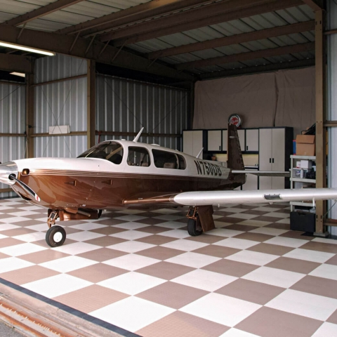 This brown and white checkered RaceDeck Diamond hangar flooring complements the brown and white plane nicely.