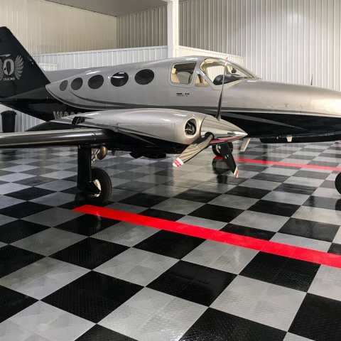 Airplane hangar with a Cessna 414. RAM - Series VI  and a RaceDeck Diamond TuffShield airplane hangar floor.
