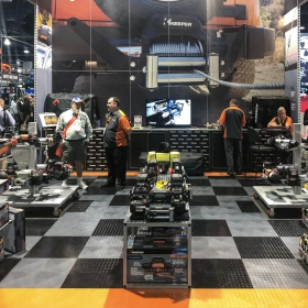 Keeper booth at SEMA with RaceDeck's TuffShield flooring in black, alloy, and orange