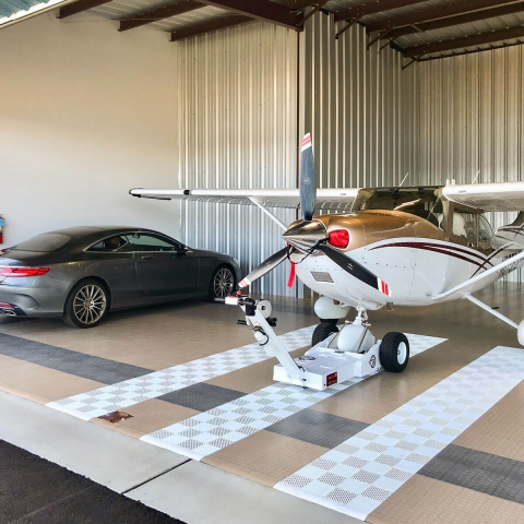 Plane and Mercedes parked in a hangar with RaceDeck CircleTrac flooring and white Free-Flow accents.