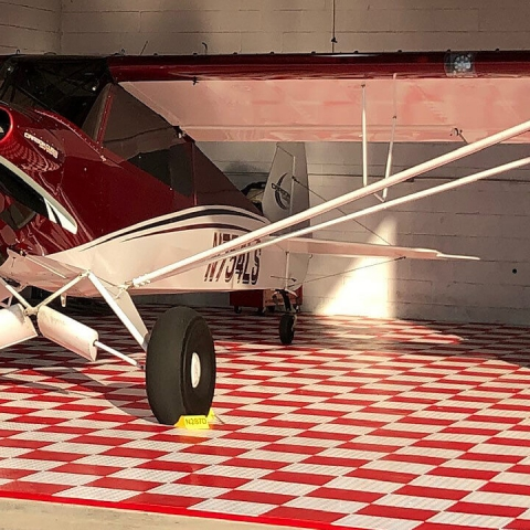 Airplane and motorcycle parked on checkered red and white RaceDeck flooring