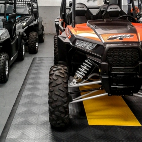 UTVs in a garage with RaceDeck Diamond parking pad