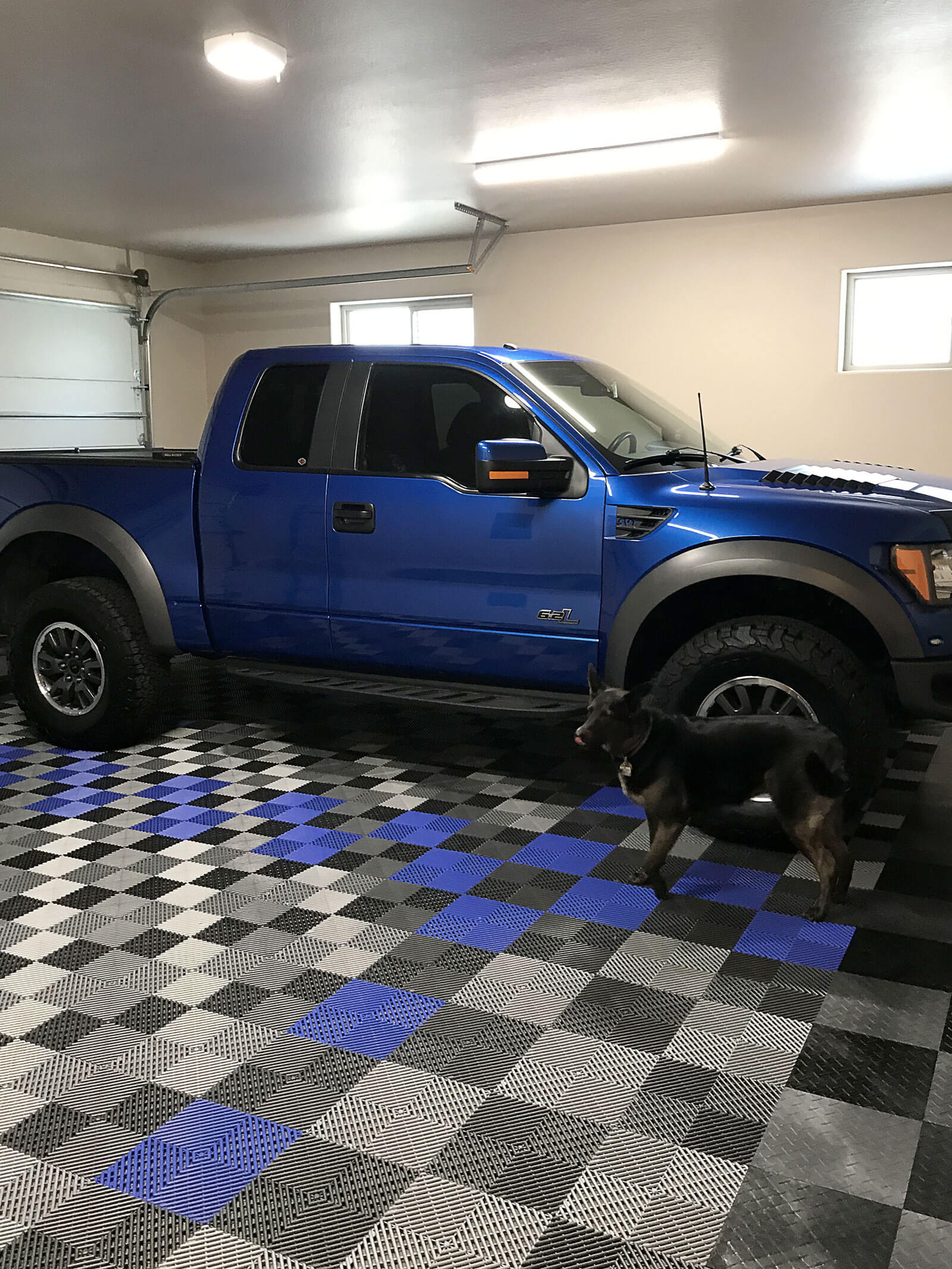 Free-Flow and RaceDeck Diamond garage in a custom design matches this blue truck and even the dog.