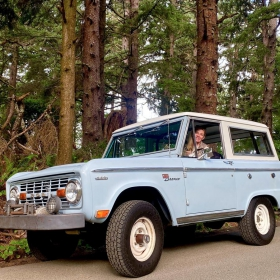 Kerry Moller taking a Ford Bronco for a drive through a forest.