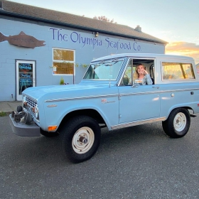 he Olympia Seafood Co. with a blue Bronco parked in the front.