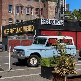 A sky blue Ford Bronco parked outside of Voodoo Doughnut in Portland Oregon with the Keep Portland Weird sign in the background.