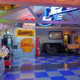 Interior view of the colorful garage; vintage memorabilia, neon signs, RaceDeck TuffShield flooring